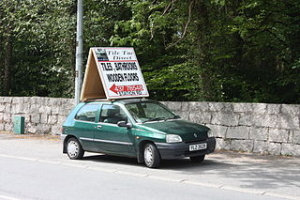Car with sign on roof is early example of mobile advertising.